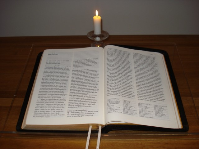 Bible with candle light